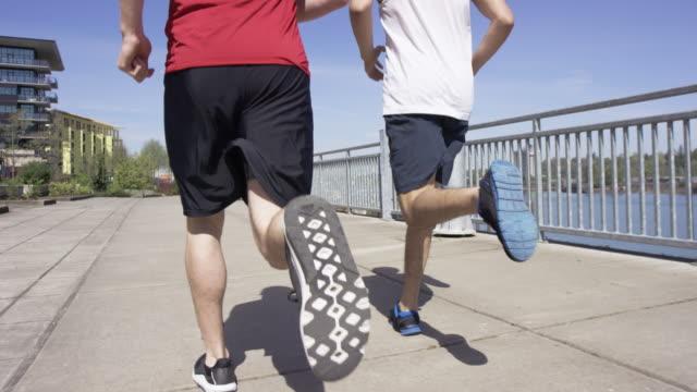 vídeos y material grabado en eventos de stock de dos corredores correr juntos en la ciudad junto al mar - bulevar