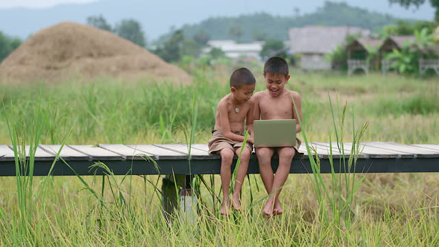 two rural boys playing with a notebook happily. on a smiling face on a wooden bridge with a background in a field means of access, the arrival of technology in the wilderness can still use the internet. - developing countries stock videos & royalty-free footage