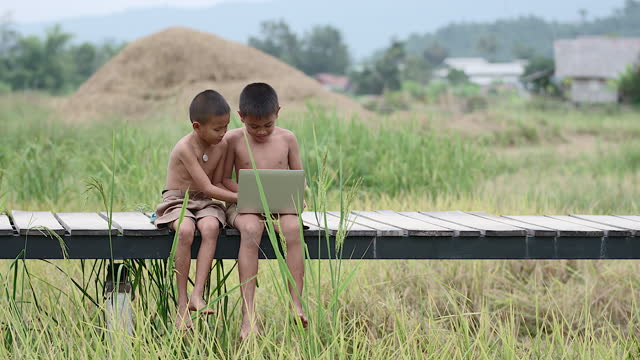 vídeos de stock e filmes b-roll de two rural boys playing with a notebook happily. on a smiling face on a wooden bridge with a background in a field means of access, the arrival of technology in the wilderness can still use the internet. - povo tailandês