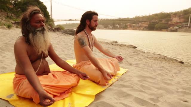 Two sage doing padmasana at ganges riverbank, Laxman Jhula, Rishikesh, Uttarakhand, India