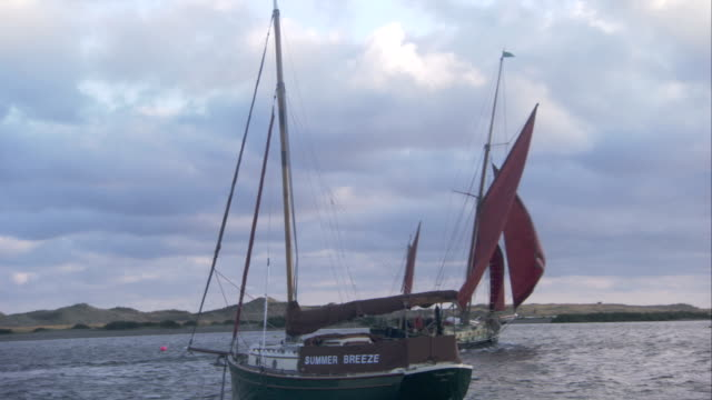 vidéos et rushes de two sailboats pass each other in the north sea off the norfolk coast. available in hd. - mer du nord
