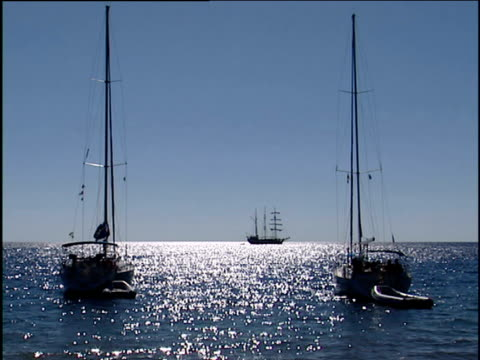 two sailing boats in sparkling blue sea silhouette of three mast ship sails passes on horizon soufriere - st lucia stock videos & royalty-free footage