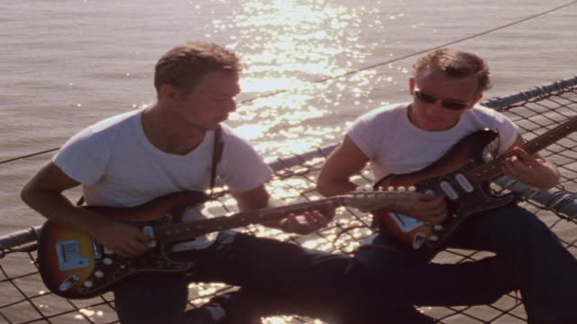 stockvideo's en b-roll-footage met tu two sailors relaxing and playing guitars on wire grille aboard lst and two pbrs passing and turning into the sunset / vietnam - rondrijden