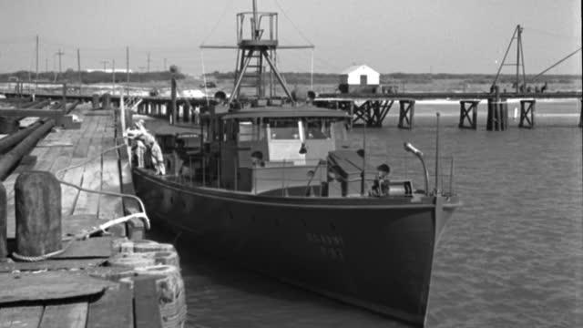 vídeos de stock e filmes b-roll de two sailors run across a wood dock, board a minesweeper and cruise through a harbor. - ancorado