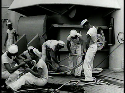 stockvideo's en b-roll-footage met two sailors walking on battleship deck at sea vs sailors coiling rope on deck int ls men eating in mess hall ms sailors eating wwii world war ii - 1942