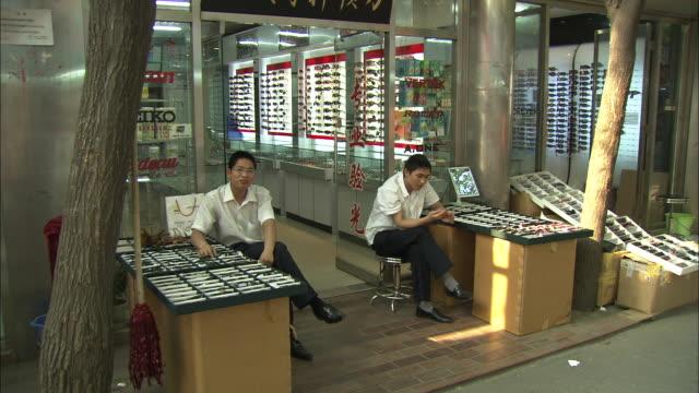 ws two salesmen sitting outside store next to cabinets with eyeglasses, beijing optical city, beijing, beijing, china - skåp med glasdörrar bildbanksvideor och videomaterial från bakom kulisserna