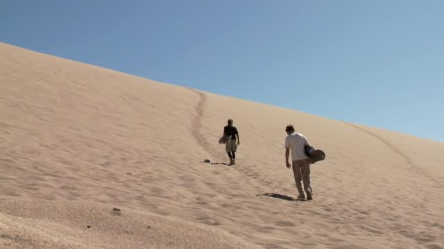 ws two sand-boarders walking slowly up sand dune / san pedro de atacama, norte grande, chile - san pedro de atacama stock videos & royalty-free footage