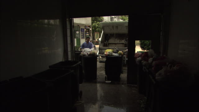 ws two sanitation workers emptying garbage bins into garbage truck, shanghai, china - dustman stock videos & royalty-free footage