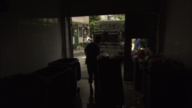 ws two sanitation workers emptying garbage bins into garbage truck, shanghai, china - garbage truck stock videos and b-roll footage