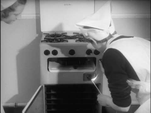 two school girls light an oven during a cookery lesson. - home economics video stock e b–roll