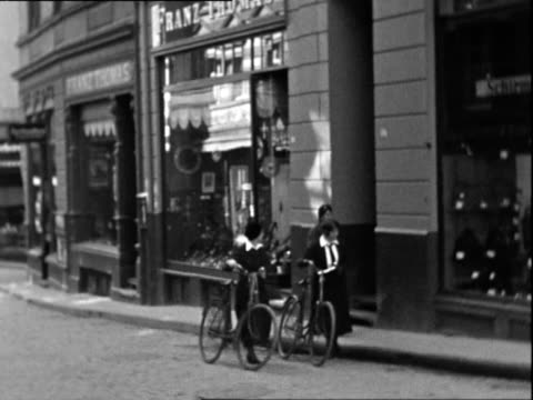 vídeos de stock e filmes b-roll de two school girls push bikes along a shopping street another woman walks two men stand storefront sells 'cigarren' window display has nazi swasitka - menos de 10 segundos