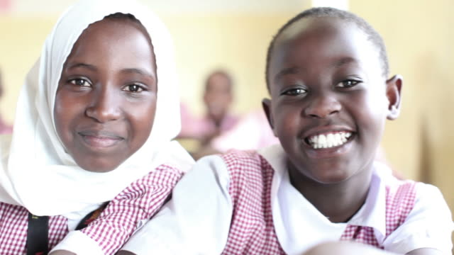 Two school girls smile in their uniforms in Kenya.
