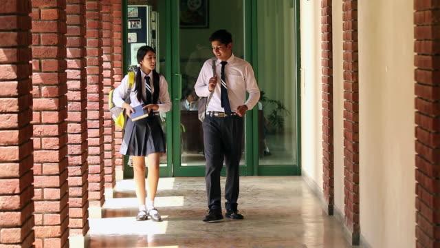 vídeos de stock, filmes e b-roll de two school students walking in the corridor, noida, uttar pradesh, india - adolescentes meninas