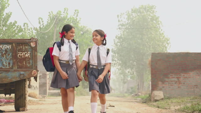Two schoolgirls walking, Delhi, India