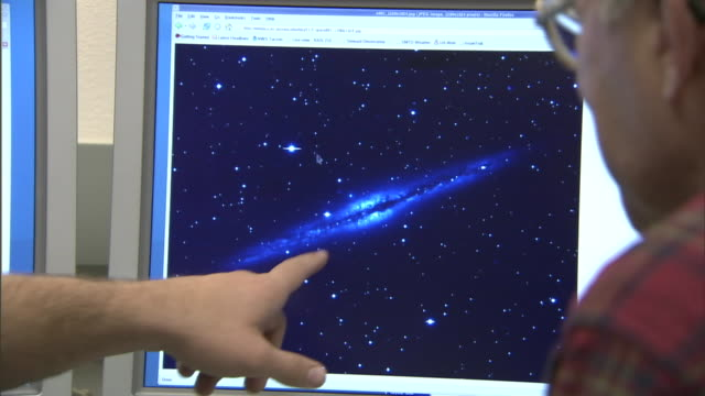 two scientists discuss an image of a galaxy on a computer screen. - astronomie stock-videos und b-roll-filmmaterial