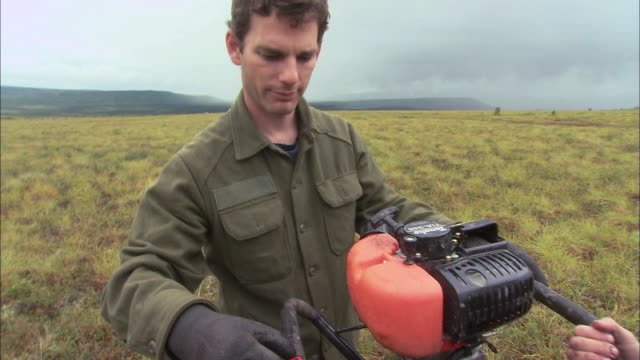 td two scientists in a field core drilling, using a mechanized apparatus / alaska, united states - letterbox format stock videos & royalty-free footage