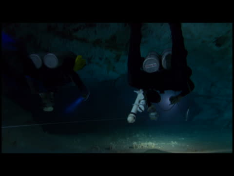 vídeos de stock, filmes e b-roll de ms two scuba diver exploring underwater cave - stalactite