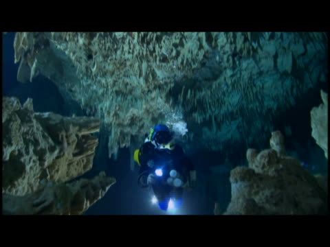 ms  pan two scuba diver exploring underwater cave - stalagmite stock videos and b-roll footage