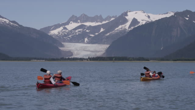 two sea kayaks paddle in the sea with glacier behind them in alaska - juneau stock videos and b-roll footage