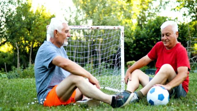 Zwei Erwachsene Senior im Fußball Uniform passen ruht nach ein