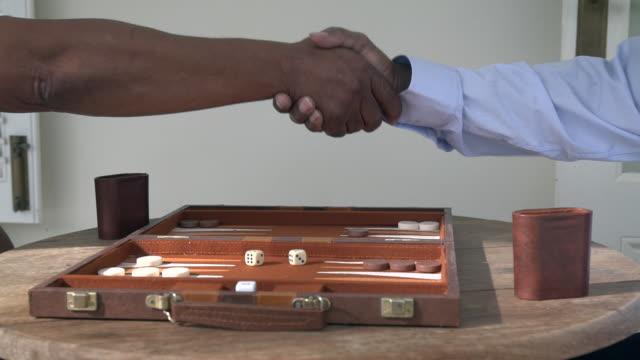 vídeos de stock, filmes e b-roll de mcu two senior african men playing backgammon on patio/ cape town/ south africa - jogo da sorte