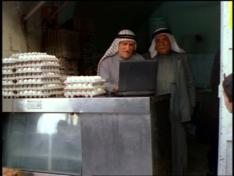 two senior arab egg vendors in kaffiyehs using laptop at booth in outdoor market / jerusalem - mature adult stock videos & royalty-free footage