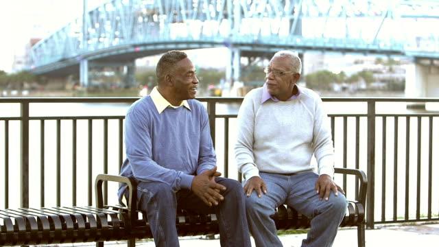zwei ältere schwarze männer am park bank sprechen - sitzbank stock-videos und b-roll-filmmaterial