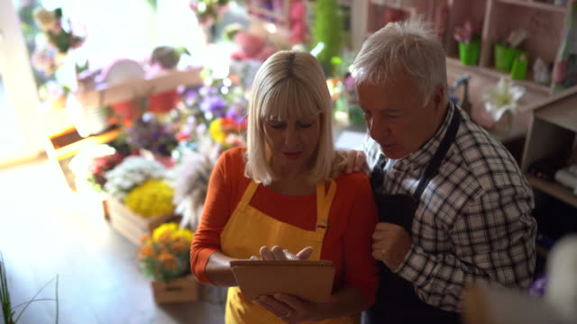 two senior florists using digital tablet at flower shop - retail occupation stock videos & royalty-free footage