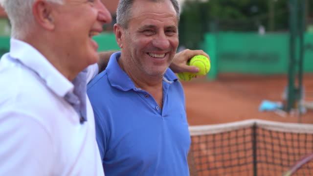 vídeos de stock, filmes e b-roll de dois amigos seniores curtindo diversão juntos após o treino na quadra de tênis - amizade masculina