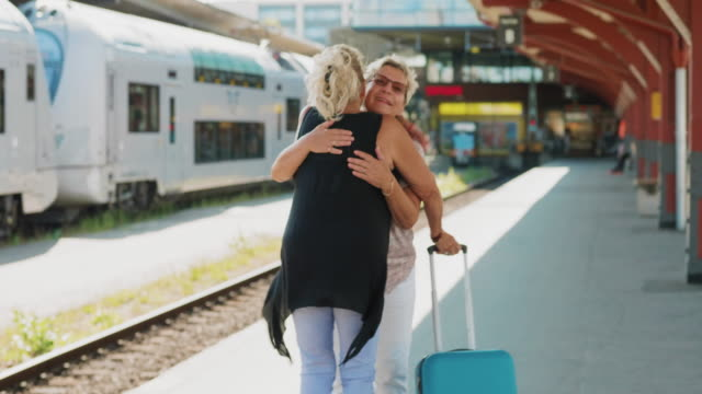 two senior friends are meeting each other at the train station - railway station stock videos & royalty-free footage