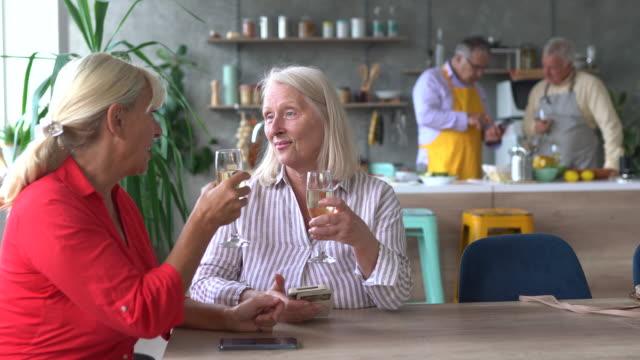 vídeos de stock, filmes e b-roll de dois amigos seniores sentados à mesa e surfando na rede enquanto seus maridos preparam comida na cozinha - idoso na internet