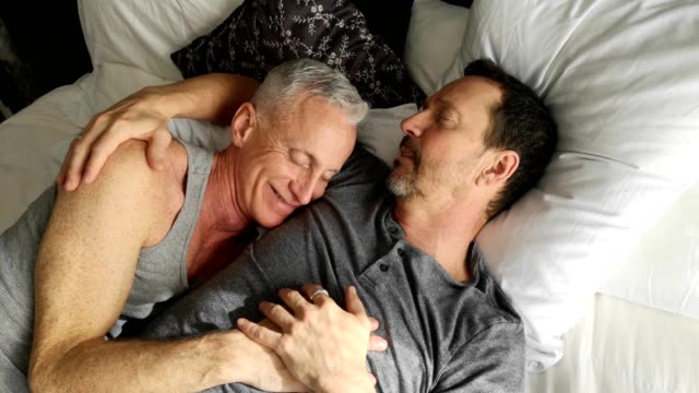 two senior gay men having a tender moment during weekend afternoon nap - affectionate stock videos & royalty-free footage