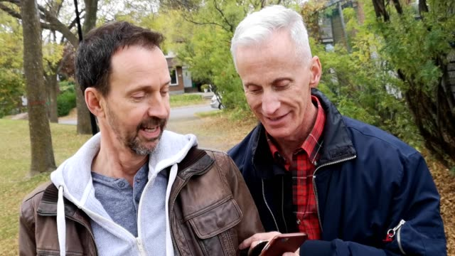 two senior gay men walking in park in autumn discussing mobile phone 4k video - mature adult stock videos & royalty-free footage