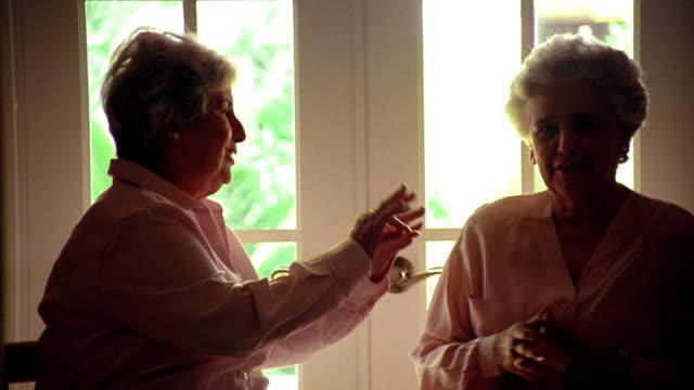 stockvideo's en b-roll-footage met ms silhouette two senior hispanic women sitting + talking with windowed door in background - tuindeur