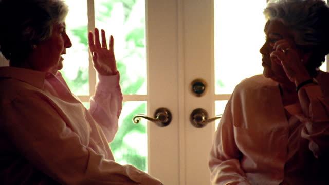 stockvideo's en b-roll-footage met ms two senior hispanic women sitting + talking with windowed door in background - tuindeur