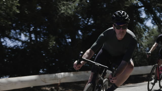 two senior male cyclists race together does winding mountain road, taking corners at high speed - mountain ridge stock videos & royalty-free footage