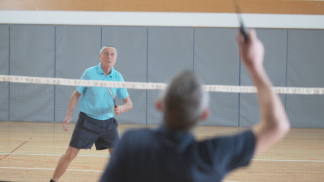 Two senior male friends playing indoor badminton