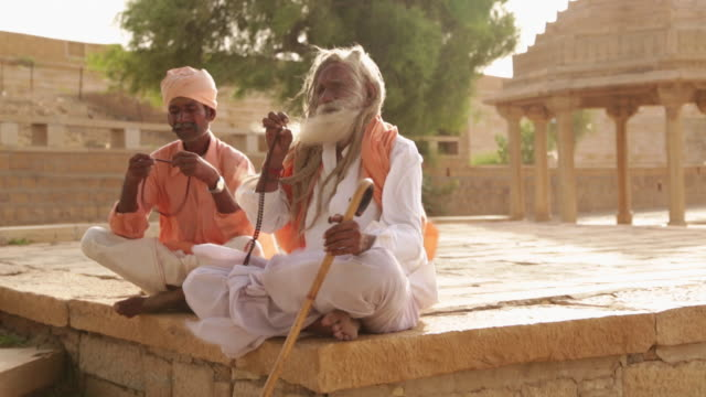 stockvideo's en b-roll-footage met two senior man worshipping, jaisalmer, rajasthan, india - in kleermakerszit