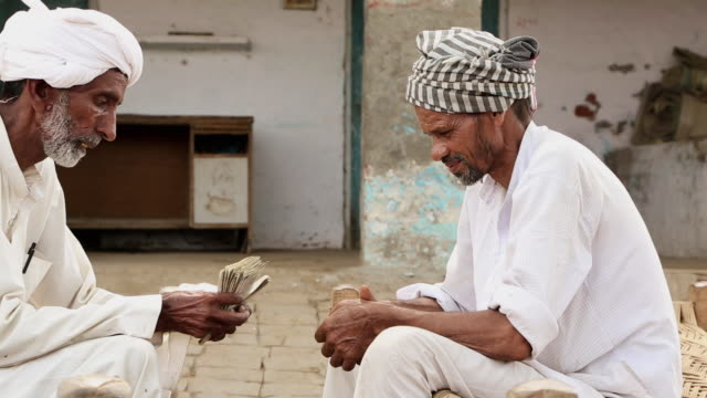 Two senior men counting indian rupees, Haryana, India