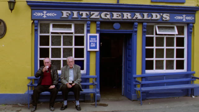 "two senior men drinking beers + sitting on bench in front of  ""fitzgerald's"" pub / avoca, ireland - pub stock videos & royalty-free footage"