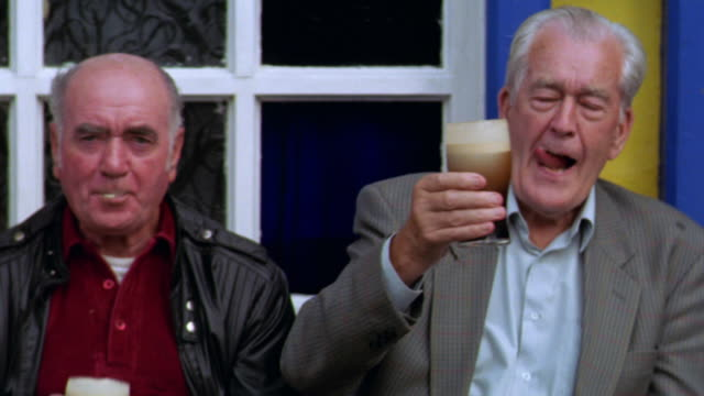 portrait two senior men drinking dark beer on bench in front of pub / avoca, ireland - alkoholisches getränk stock-videos und b-roll-filmmaterial