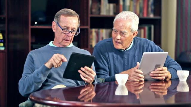 two senior men talking, using digital tablets - reading glasses stock videos & royalty-free footage