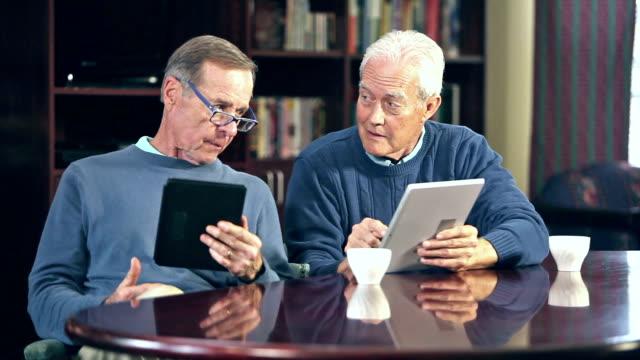 two senior men talking, using digital tablets - white hair stock videos & royalty-free footage