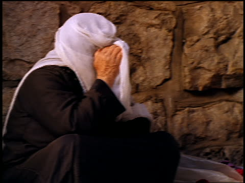pan two senior muslim women sitting on ground by stone wall talking outdoors / jerusalem - forgiveness stock videos and b-roll footage