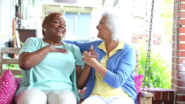 Two senior woman talking, laughing on front porch