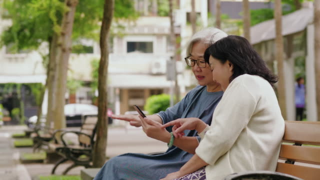 Two senior women are having fun using social media on a smart phone