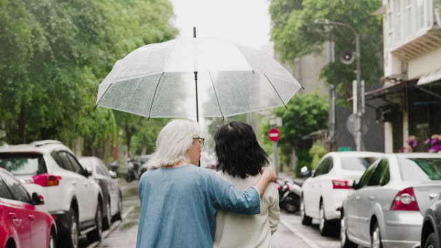 Two senior women are on a walk in the city on a rainy day