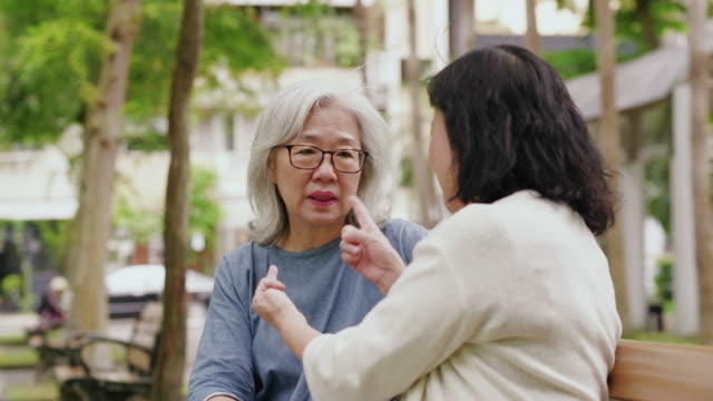 Two senior women are talking and spending time together in a public park