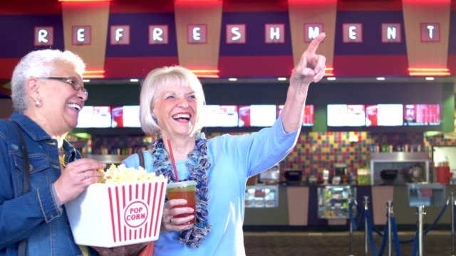 two senior women at movie theater concession stand - lobby stock videos & royalty-free footage