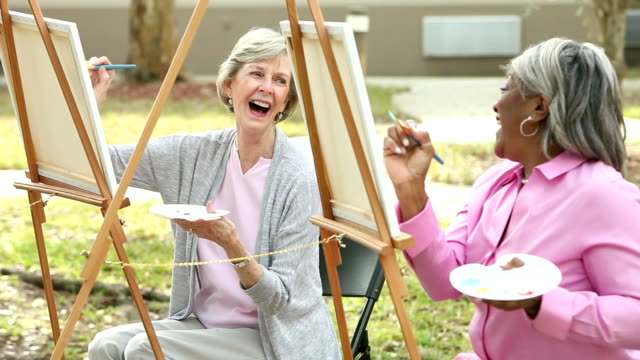 two senior women chatting while painting on canvas - pittore video stock e b–roll